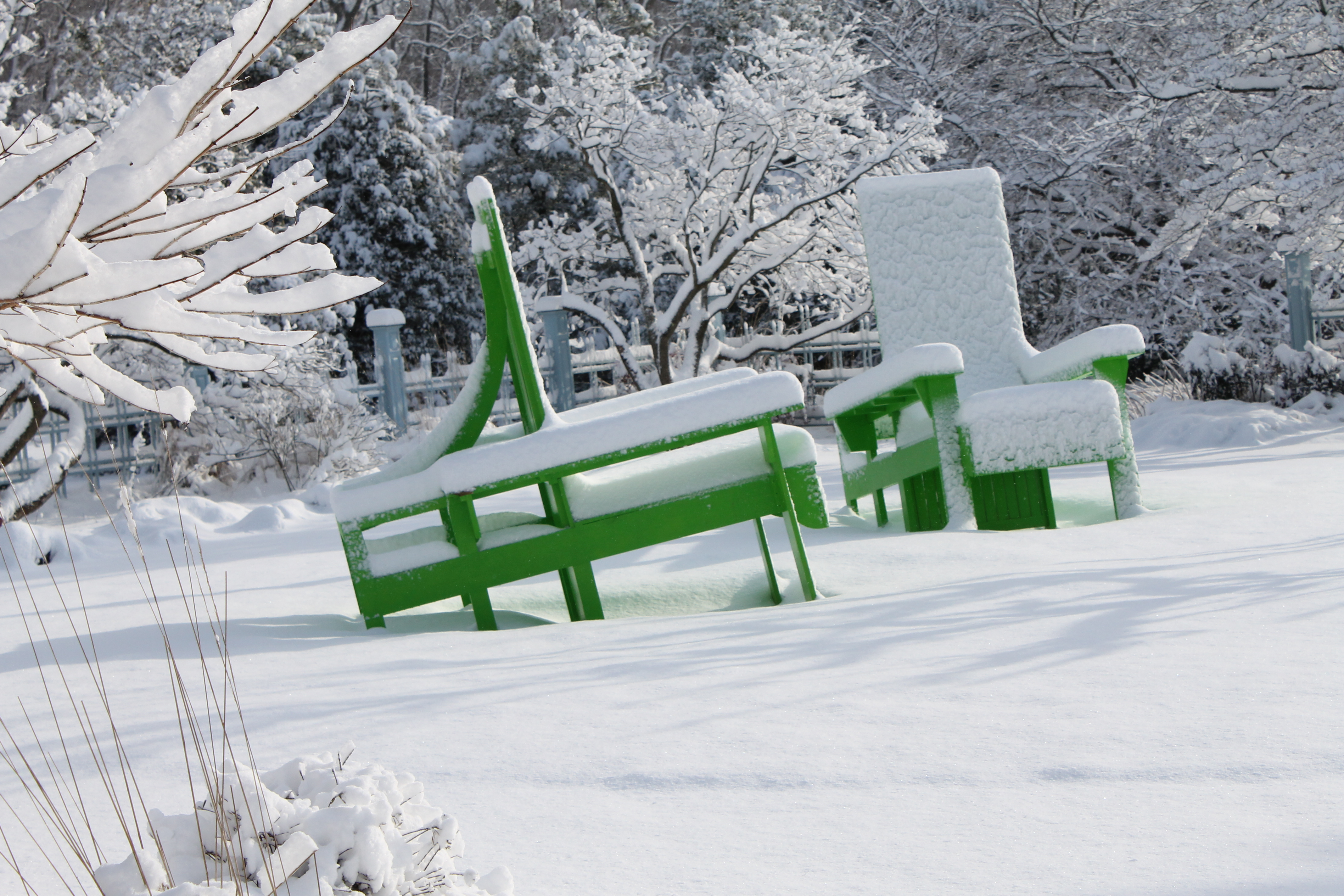 Snow on the big green chairs.