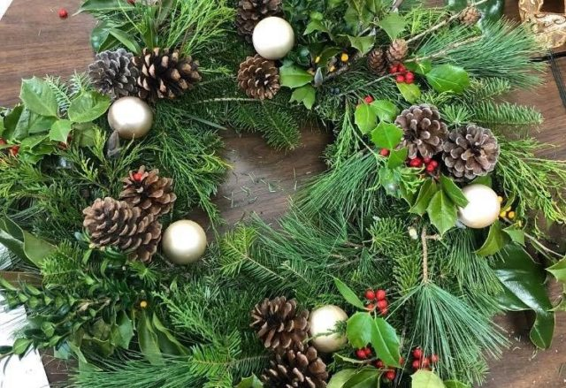 evergreen wreath decorated with sprigs of holly and pinecones